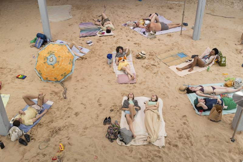 """This image released by the Brooklyn Academy of Music shows a scene from the climate change opera """"Sun and Sea"""" as performed at Venice Biennale 2019. The production is embarking on a US tour this month, starting with performances at the Brooklyn Academy of Music. (Andrej Vasilenko/BAM via AP)"""
