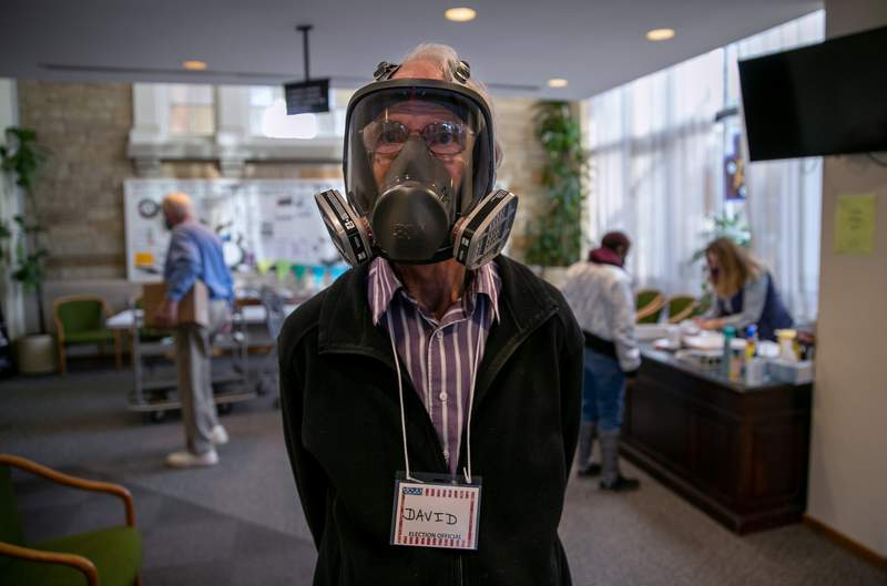 Election inspector David Hopkinson wears a full-face ventilator as a protection against Covid-19 while working at the Emanuel First Lutheran School polling center on Nov. 03 in Lansing, Michigan.