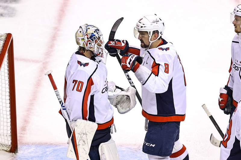 TORONTO, ONTARIO - AUGUST 18:  Braden Holtby #70 and Alex Ovechkin #8 of the Washington Capitals celebrate their teams 3-2 win against the New York Islanders in Game Four of the Eastern Conference First Round during the 2020 NHL Stanley Cup Playoffs at Scotiabank Arena on August 18, 2020 in Toronto, Ontario. (Photo by Elsa/Getty Images)