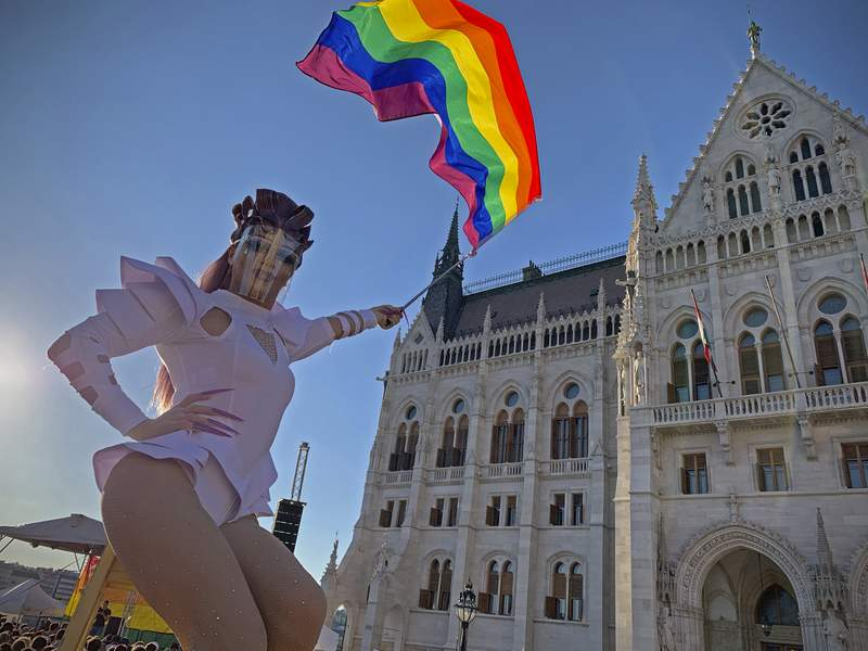 A drag queen waves a rainbow flag during an LGBT rights demonstration in front of the Hungarian Parliament building in Budapest, Hungary on June. 14, 2021. During the protest human rights activists called on lawmakers in Hungary to reject legislation banning any content portraying or promoting homosexuality or sex reassignment to anyone under 18. The bills, aiming at fighting pedophilia, have various amendments which would outlaw any depiction or discussion of different gender identities to youth in the public sphere. (AP Photo/Bela Szandelszky)