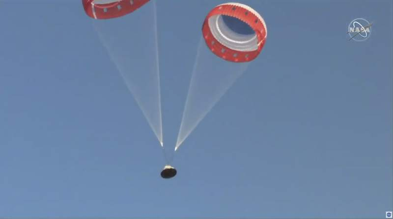 In this image made from a video provided by NASA  parachutes guide the Starliner capsule to the ground after a test of Boeing's crew capsule's launch abort system in White Sands Missile Range in N.M., on Monday, Nov. 4, 2019. The capsule carried no astronauts Monday morning, just a test dummy. (NASA via AP)