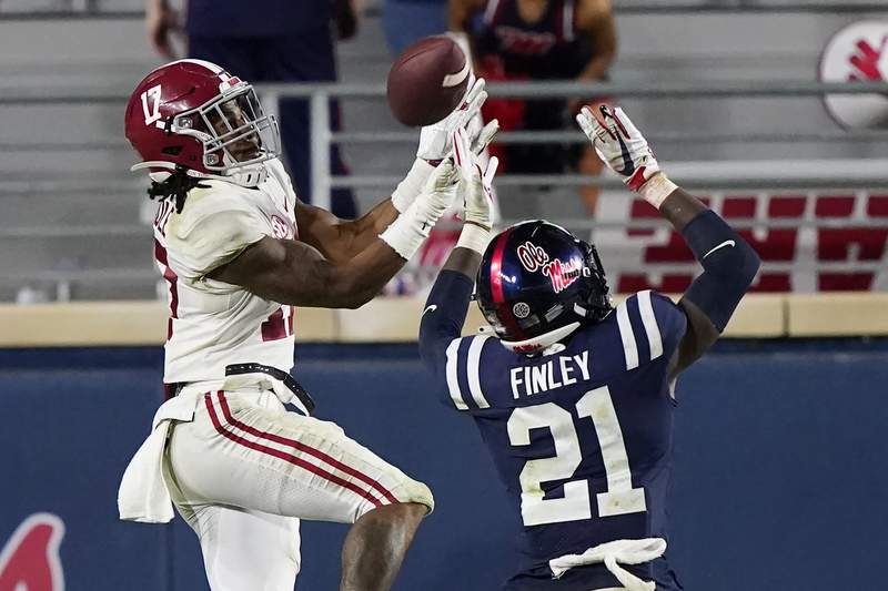 Alabama wide receiver Jaylen Waddle (17) pulls in a pass over Mississippi defensive back A.J. Finley (21) during the second half of an NCAA college football game in Oxford, Miss., Saturday, Oct. 10, 2020. Alabama won 63-48. (AP Photo/Rogelio V. Solis)