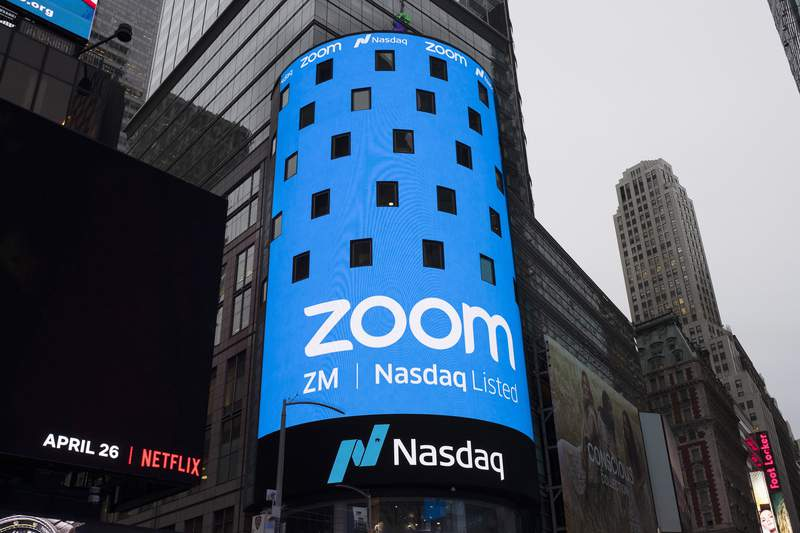 FILE - This April 18, 2019, file photo shows a sign for Zoom Video Communications ahead of the company's Nasdaq IPO in New York.  (AP Photo/Mark Lennihan, File)
