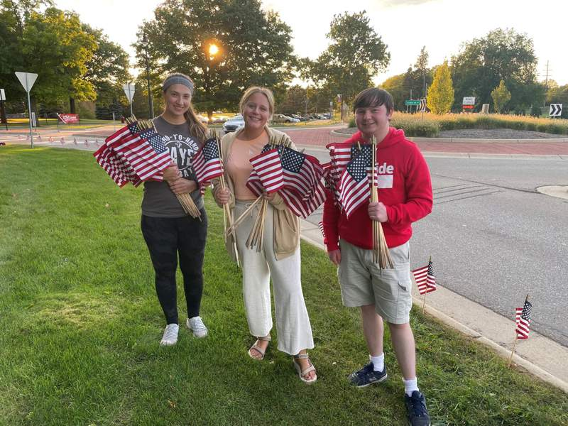 Concordia University Ann Arbor students place hundreds of flags along Geddes Road at sunset on Sept. 9, 2021.