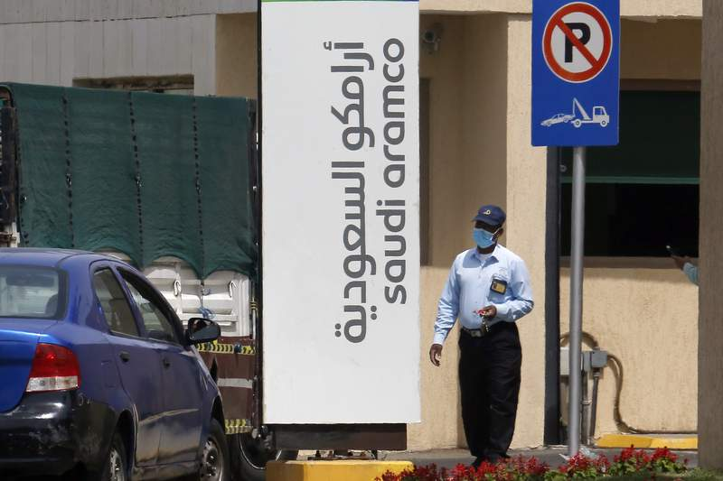 FILE - In this March 9, 2020, file photo, a security person wears a mask as he checks vehicles entering a compound for Saudi Aramco in Jiddah, Saudi Arabia. Saudi Aramco's net income plunged by 50% in the first half of the year, according to figures published Sunday, Aug. 9, 2020, offering a revealing glimpse into the impact of the coronavirus pandemic on one of the world's biggest oil producers. (AP Photo/Amr Nabil, File)