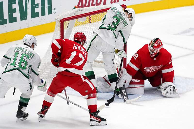 Dallas Stars' Joe Pavelski (16) looks on as Detroit Red Wings' Filip Hronek (17) helps goaltender Thomas Greiss (29) defend against pressure from defenseman John Klingberg (3) in the overtime of an NHL hockey game in Dallas, Monday, April 19, 2021. (AP Photo/Tony Gutierrez)