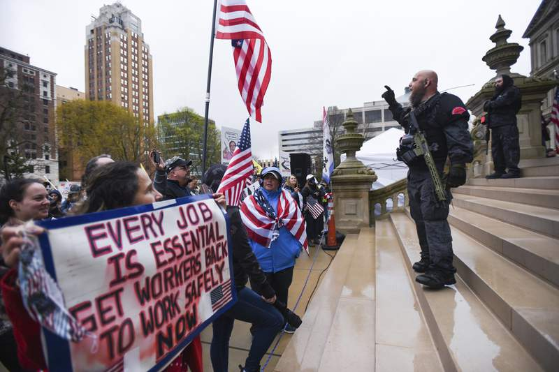 Members of the Michigan Liberty Militia, including Phil Robinson, right, join protesters at a rally at the state Capitol in Lansing, Mich., Thursday, April 30, 2020. Hoisting American flags and handmade signs, protesters returned to the state Capitol to denounce Gov. Gretchen Whitmer's stay-home order and business restrictions due to COVID-19, while lawmakers met to consider extending her emergency declaration hours before it expires. (Matthew Dae Smith/Lansing State Journal via AP)