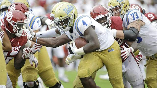 Running back Bolu Olorunfunmi #4 of the UCLA Bruins tries to break through the Oklahoma Sooners defense at Gaylord Family Oklahoma Memorial Stadium on September 8, 2018 in Norman, Oklahoma. The Sooners defeated the Bruins 49-21. (Photo by Brett Deering/Getty Images)