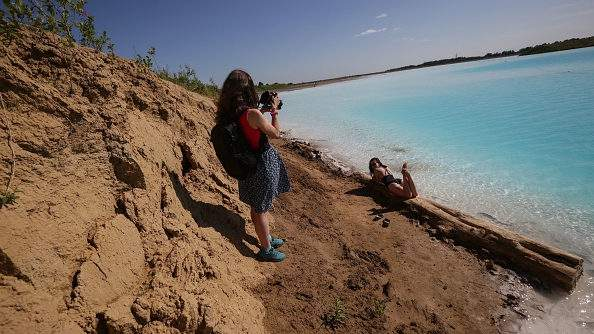 """A young woman poses for pictures by a Novosibirsk energy plant's ash dump site, nicknamed the local """"Maldives,"""" on July 11, 2019 (ROSTISLAV NETISOV/AFP/Getty Images)."""
