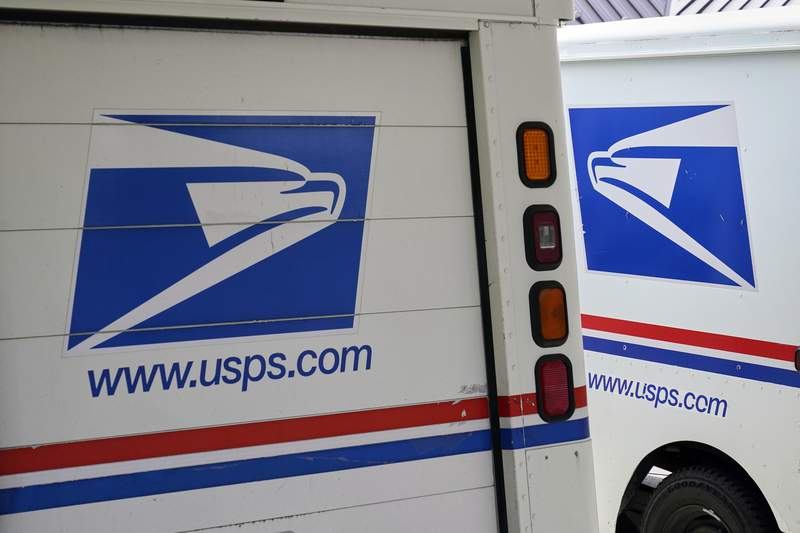 FILE - In this Aug. 18, 2020, file photo, mail delivery vehicles are parked outside a post office in Boys Town, Neb. (AP Photo/Nati Harnik, File)