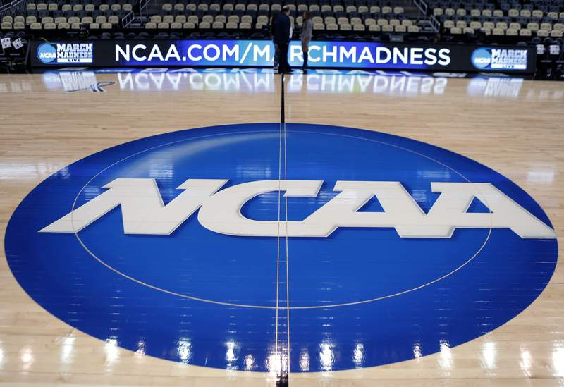 FILE - In this March 18, 2015, file photo, the NCAA logo is displayed at center court as work continues at The Consol Energy Center in Pittsburgh, for the NCAA college basketball tournament. The NCAA took a significant step toward allowing all Division I athletes to transfer one time without sitting out a season of competition. A plan to change the waiver process is expected to be presented to the Division I Council in April, 2020. If adopted, new criteria would go into effect for the 2020-21 academic year and be a boon for athletes in high-profile sports such as football and men's and women's basketball. (AP Photo/Keith Srakocic, File)
