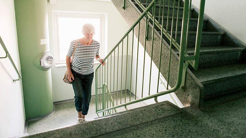 A woman climbs stairs in a stairwell.