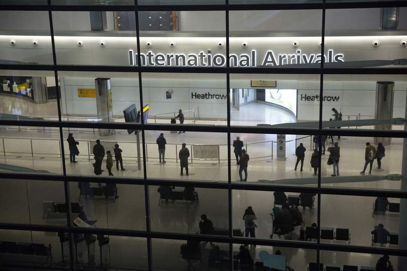 FILE In this file photo dated Tuesday, Jan. 26, 2021, people in the arrivals area at Heathrow Airport in London, during England's coronavirus lockdown.  The return of international travel is key to economic recovery across Europe, particularly for countries that rely more heavily on tourism, according to figures released Thursday June 24, 2021, from the World Travel and Tourism Council.(AP Photo/Matt Dunham, FILE)