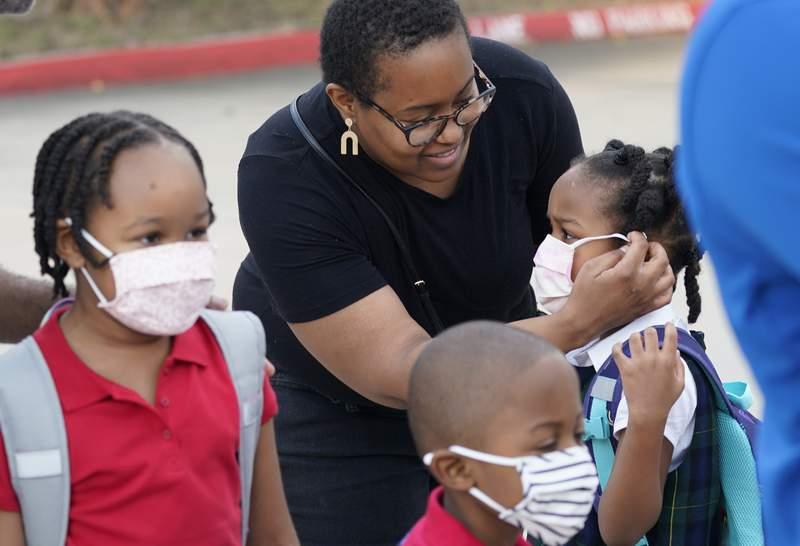 FILE - In this Aug. 17, 2021, file photo Leandra Walker, center, helps her daughter Mila Walker, 5, with her mask before she enters school with her siblings Olivia, 7, left, and her twin Max for the first day of classes in Richardson, Texas. A new poll finds that a majority of Americans support mask and vaccine mandates for students and teachers in K-12 schools. The poll from the Associated Press-NORC Center for Public Affairs Research finds that about 6 in 10 Americans say masks and vaccines should be required in schools. (AP Photo/LM Otero, File)