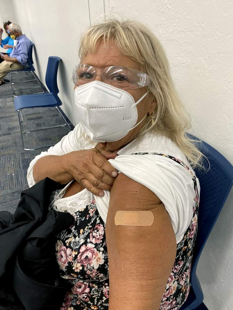 In this photo provided by Terry Beth Hadler , the 69-year-old, poses after receiving a dose of a COVID-19 vaccine on Tuesday, Dec. 29, 2020, at a Bonita Springs, Fla. library where Lee County officials were administering the vaccine on a first come, first-served basis to people 65 or older. Hadler, who waited overnight in line for 14 hours with hundreds of other seniors, said a brawl nearly erupted before dawn on Tuesday when line-cutters joined the crowd. I'm afraid that the event was a super-spreader. I was scared there. I was petrified, she said. (Courtesy of Terry Beth Hadler via AP)