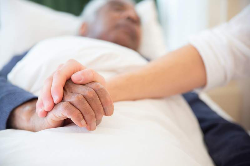 A volunteer sits with a hospice patient.