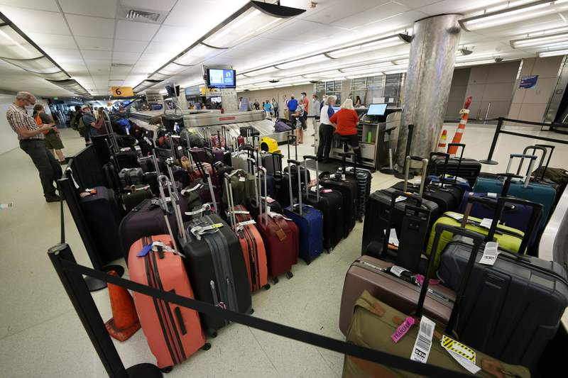 Baggage stacks up from delayed travellers in the baggage claim area in Denver International Airport Wednesday, June 16, 2021, in Denver.  The Biden administration is planning to require that airlines refund fees on checked baggage if the bags get seriously delayed. The proposal would also require refunds for fees on extras like internet access if the airline fails to provide the service during the flight.   (AP Photo/David Zalubowski)