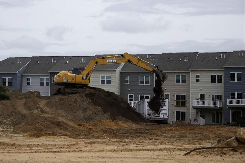 A construction crew loads dirt on a building site, Monday, May 18, 2020 in East Greenwich, N.J. (AP Photo/Matt Slocum)