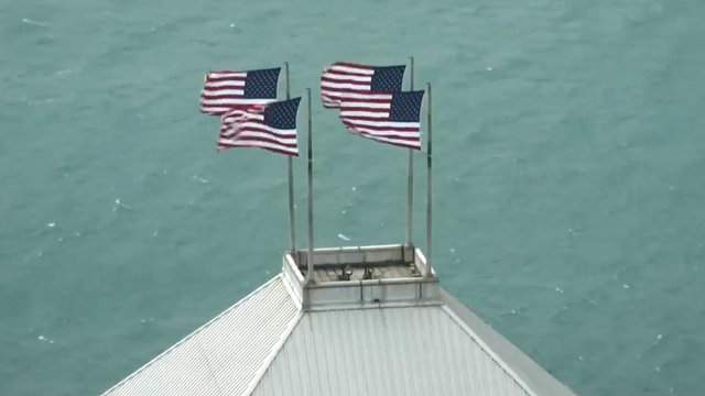 Flags blow in the wind atop 150 West Jefferson Avenue on May 4, 2018 in Downtown Detroit. (WDIV)