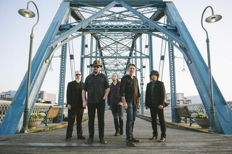 This image released by Big Hassle shows members of Drive-By Truckers, from left, Brad Morgan, Patterson Hood, Matt Patton, Mike Cooley and Jay Gonzalez posing in front of the Walnut Street Bridge in Chattanooga, Tenn. The band's new disc, The Unraveling, released on Friday. (Andy Tenille via AP)