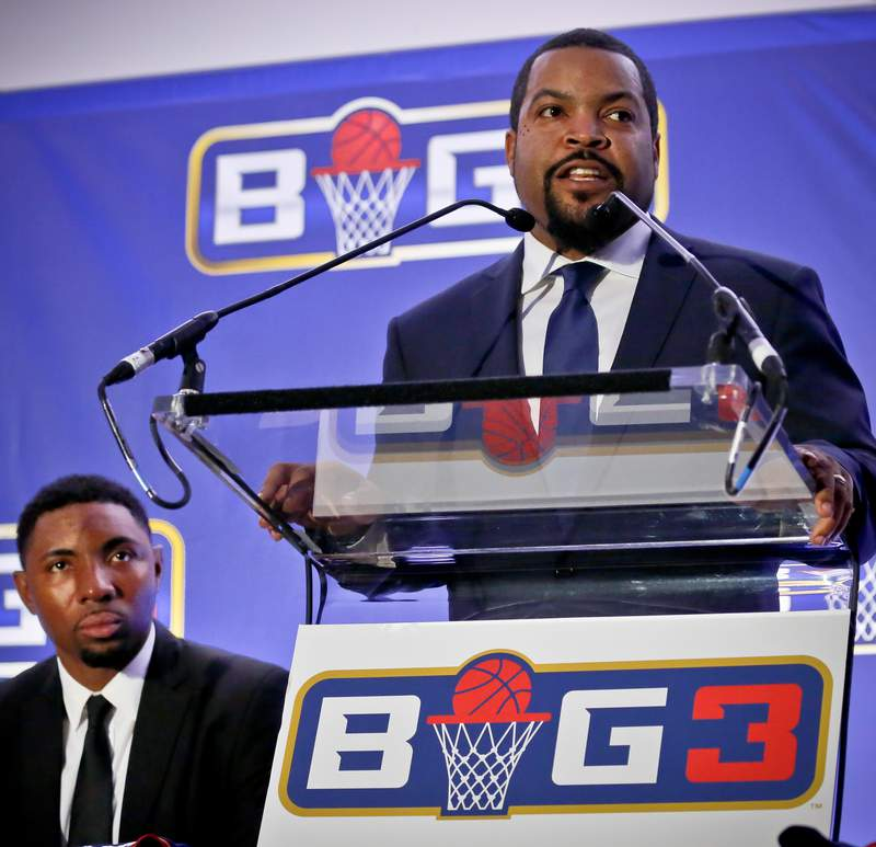 FILE - In this Jan. 11, 2017, file photo, former NBA player and players union deputy Roger Mason, left, listens as entertainer Ice Cube, right, announces the launch of the BIG3, a new 3-on-3 professional basketball league, in New York. Hundreds of sports-related businesses got in line for the government-funded Payroll Protection Plan designed to cushion the economic impact of the COVID-19 pandemic. None of the four North American major sports leagues  the NFL, NBA, NHL and Major League Baseball  applied, but both Major League Soccer and the National Women's Soccer League were represented. Rapper Ice Cube's 3-on-3 basketball league says it returned almost half of the $1.6 million it received, but givebacks were rare. (AP Photo/Bebeto Matthews, File)