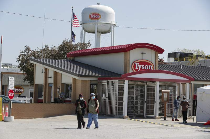 FILE - In this May 7, 2020, file photo, workers enter and leave the Tyson Foods pork processing plant in Logansport, Ind. Tyson Foods is planning to open medical clinics at several of its U.S. plants to improve the health of workers at the same time it is under pressure to better protect them from the coronavirus. (AP Photo/Michael Conroy, File)
