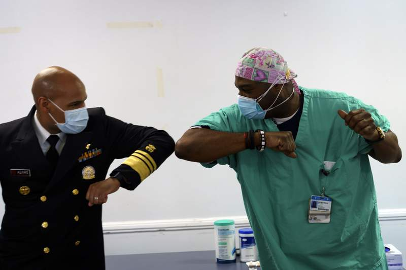 Surgeon General of the U.S. Jerome Adams, left, elbow-bumps Emergency Room technician Demetrius Mcalister after Mcalister got the Pfizer COVID-19 vaccination at Saint Anthony Hospital in Chicago, on Tuesday, Dec. 22, 2020. (Youngrae Kim/Chicago Tribune via AP, Pool)