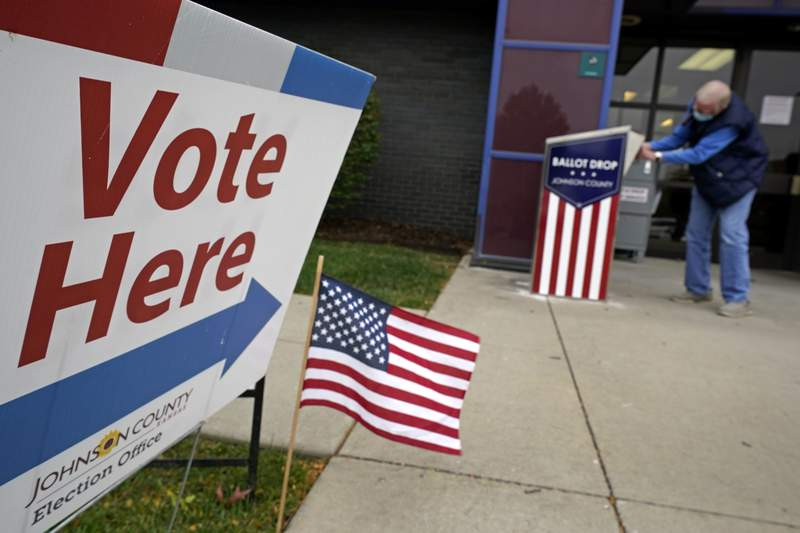 A voter deposits his advance ballot in a dropbox Tuesday, Oct. 20, 2020, in Mission, Kan. (AP Photo/Charlie Riedel, File)