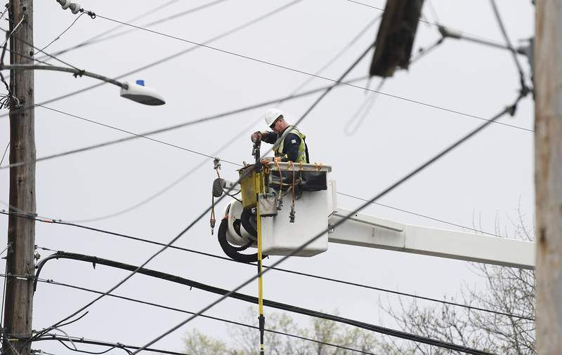 A PPL lineman works on power lines on High and Arch Streets, after strong winds moved through the area in the morning on Monday, April 13, 2020, in Wilkes-Barre, Pa. (Mark Moran/The Citizens' Voice via AP)