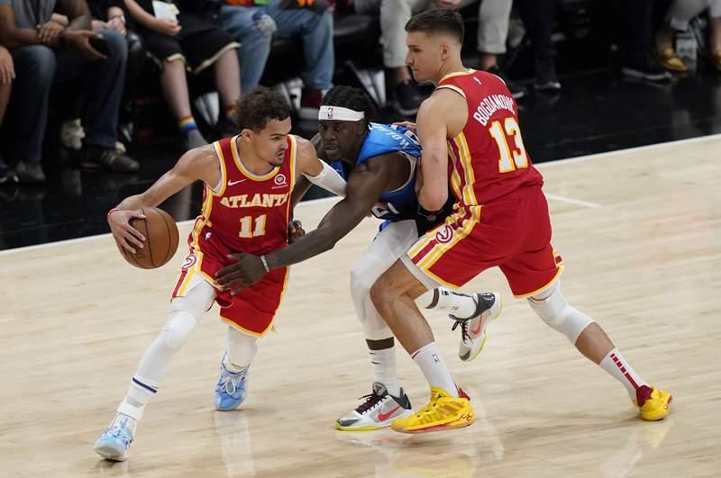Atlanta Hawks' Trae Young (11) drives around Milwaukee Bucks' Jrue Holiday (21) as Hawks' Bogdan Bogdanovic (13) sets a screen during the second half of Game 3 of the NBA Eastern Conference basketball finals, Sunday, June 27, 2021, in Atlanta. (AP Photo/Brynn Anderson)