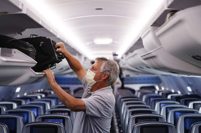 FILE - In this May 28, 2020, file photo, a passenger wears personal protective equipment on a Delta Airlines flight after landing at Minneapolis-Saint Paul International Airport, in Minneapolis. (AP Photo/John Minchillo, File)