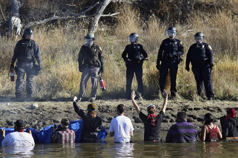 FILE - In this Nov. 2, 2016, file photo, dozens of protestors demonstrating against the expansion of the Dakota Access Pipeline wade in cold creek waters confronting local police, near Cannon Ball, N.D. Federal and state lawyers will meet in North Dakota next week to negotiate a settlement for money that the state claims it spent on policing protests against the Dakota Access oil pipeline. North Dakota filed a lawsuit against the U.S. Army Corps of Engineers in 2019, seeking to recover more than $38 million in damages from the monthslong pipeline protests almost five years ago. (AP Photo/John L. Mone, File)