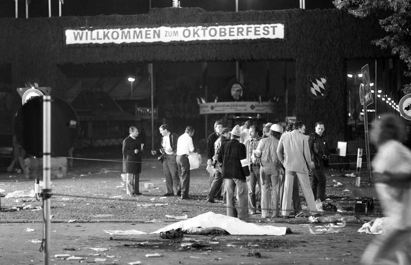 """FILE - In this Spt. 26, 1980 file photo, with welcoming gate of the main entrance in rear a victim lies in front of a rescue team on the scene of a bombing blast at Munich's """"Oktoberfest"""" beer festival in Munich, Germany. German prosecutors said Wednesday that they have closed their investigation into a deadly far-right attack with thirteen people killed and more than 200 wounded on Munich's Oktoberfest in 1980, more than five years after they revived the probe in hopes that new testimony might point to previously unknown co-conspirators.  The dead included the attacker, student Gundolf Koehler, a supporter of a banned far-right group. (AP Photo/Dieter Endlicher, FILE)"""