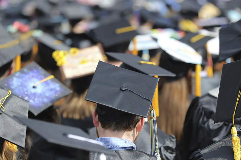 FILE - In this May 5, 2018, file photo, students attend the University of Toledo commencement ceremony in Toledo, Ohio. Colleges across the U.S. have begun cancelling and curtailing spring graduation events amid fears that the new coronavirus will not have subsided before the stretch of April and May when schools typically invite thousands of visitors to campus to honor graduating seniors. (AP Photo/Carlos Osorio, File)