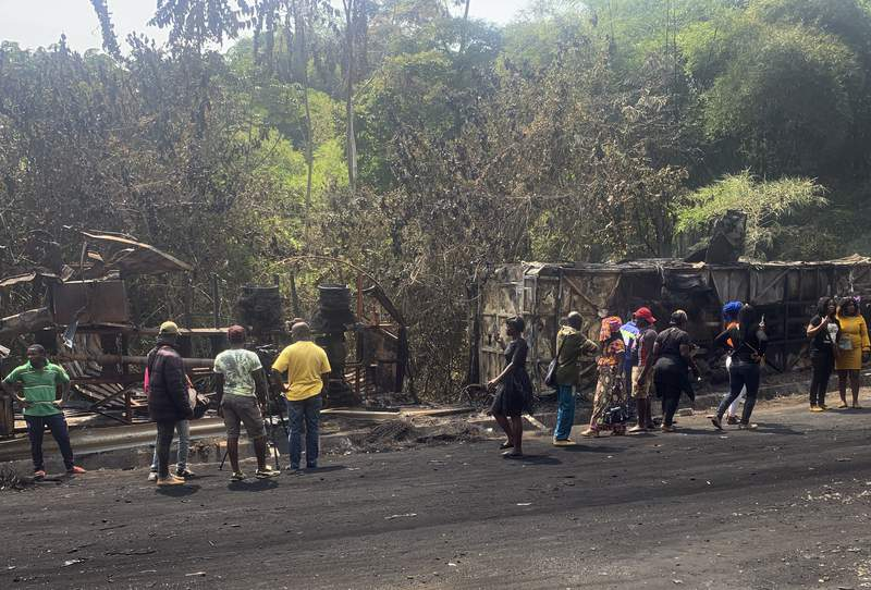 People gather at the scene of a bus crash in Santchou village in western Cameroon Wednesday, Jan. 27, 2021. At least 53 people have died and 21 others were injured in Cameroon when the bus collided with a truck early Wednesday in a village in the western part of the country, officials said. (AP Photo)