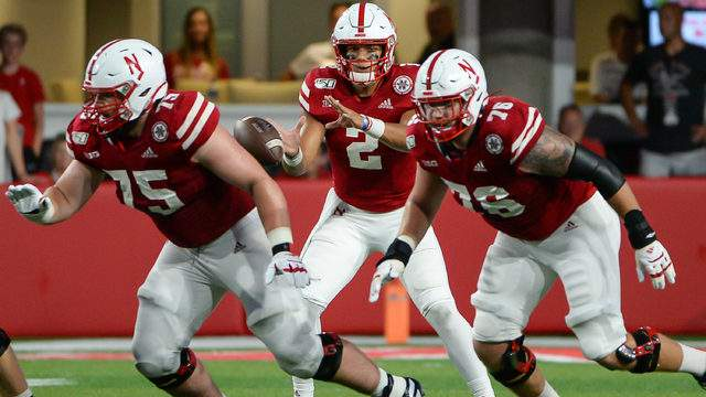 Quarterback Adrian Martinez #2 of the Nebraska Cornhuskers takes a snap as offensive lineman Trent Hixson #75 and offensive lineman Brenden Jaimes #76 block against the Northern Illinois Huskies at Memorial Stadium on September 14, 2019 in Lincoln, Nebraska. (Photo by Steven Branscombe/Getty Images)