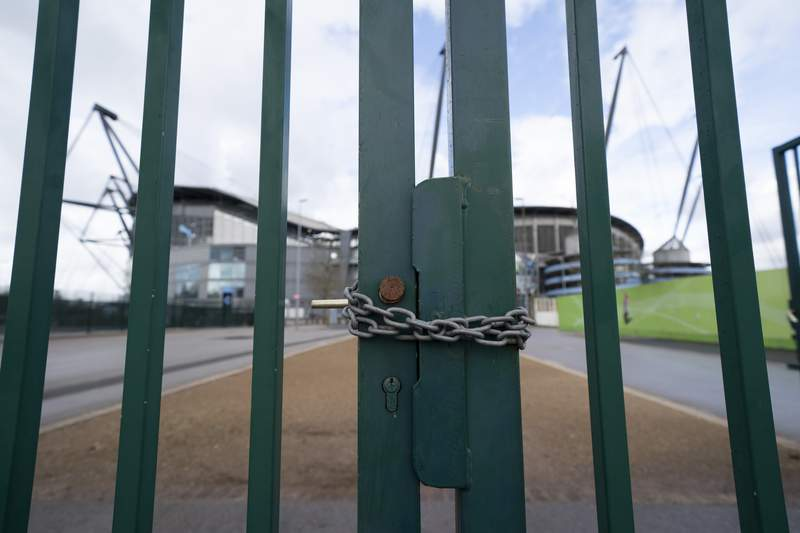 A locked gate is seen by the Etihad Stadium where Manchester City was due to play Burnley in an English Premier League soccer match Saturday March 14, 2020, after all English soccer games were cancelled due to the spread of the COVID-19 Coronavirus. For most people, the new COVID-19 coronavirus causes only mild or moderate symptoms, but for some it can cause more severe illness. (AP Photo/Jon Super)