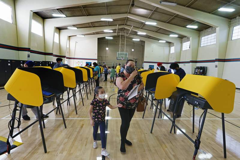 East Los Angeles voter Laura Cortez, 54, with her granddaughter Daniela 6, walk after casting her ballot in-person on Election Day inside the Ruben F. Salazar Park recreation center, an official vote center in East Los Angeles, on Tuesday, Nov. 3, 2020. Nearly 12.8 million people voted before Tuesday, signaling what could be a record turnout. (AP Photo/Damian Dovarganes)