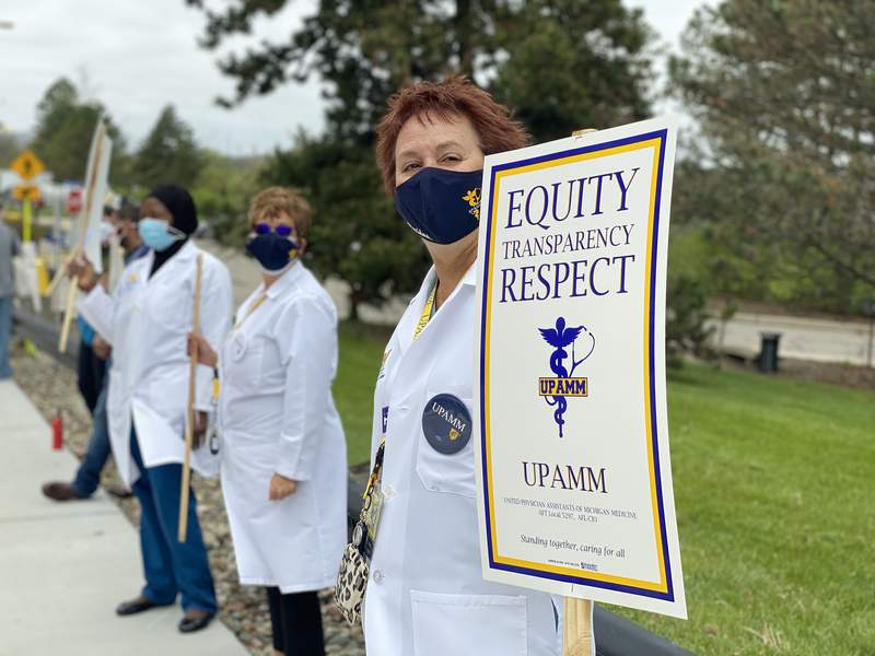 Jill Hasen, president of United Physician Assistants of Michigan Medicine, holds a sign during a rally outside U-M Hospital in support of union negotiators on May 4, 2021.
