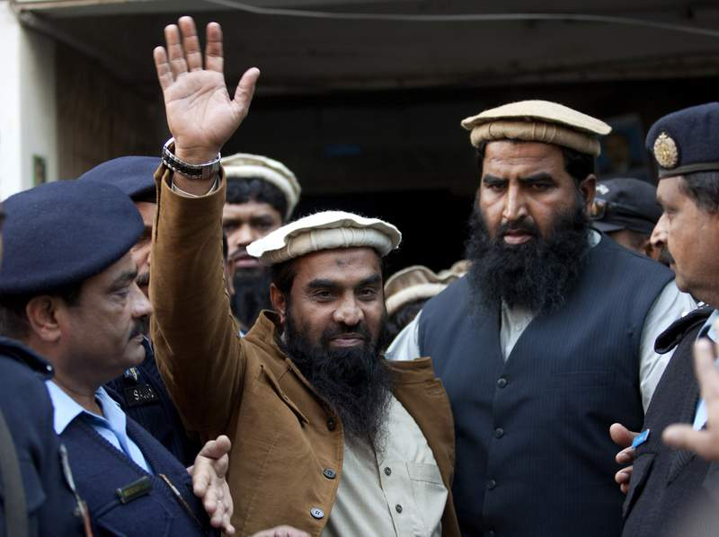 FILE - In this Thursday, Jan. 1, 2015, file photo, police officers escort Zaki-ur-Rehman Lakhvi, center, the main suspect of the Mumbai terror attacks in 2008, after his court appearance in Islamabad, Pakistan. A Pakistani court on Friday, Jan. 8, 2021, convicted and sentenced the senior militant leader Lakhvi to five years in jail in a case of terror financing, the country's counter-terrorism department in the eastern Punjab province said. (AP Photo/B.K. Bangash, File)