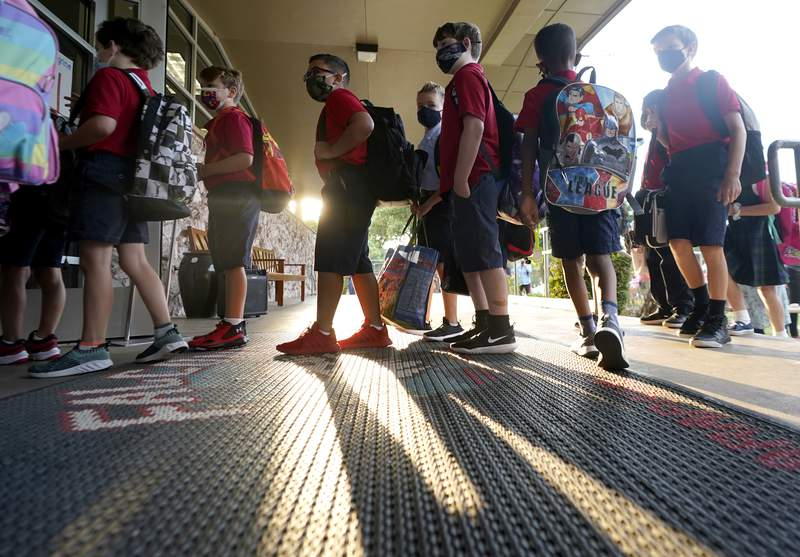 FILE - In this Aug. 17, 2021, file photo, wearing masks to prevent the spread of COVID-19, elementary school students line up to enter school for the first day of classes in Richardson, Texas. As COVID-19 cases surge, a majority of Americans say they support mask mandates for students and teachers in K-12 schools, but their views are sharply divided along political lines. (AP Photo/LM Otero, File)