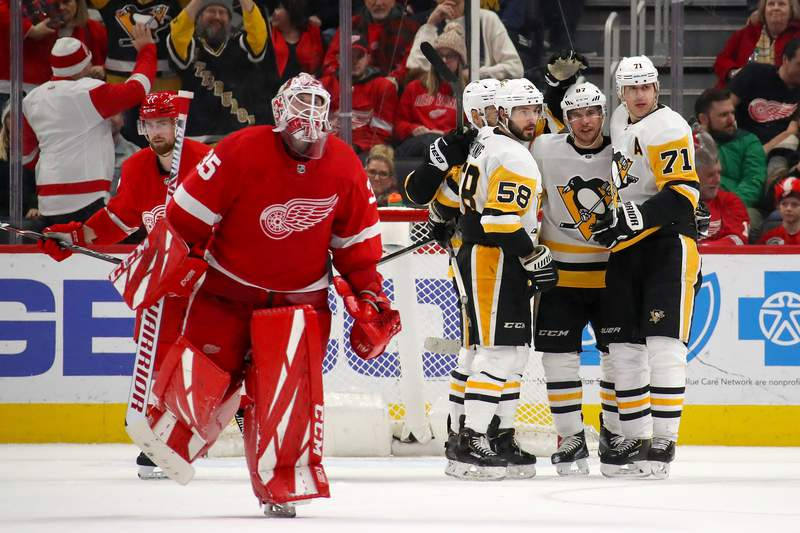 DETROIT, MICHIGAN - JANUARY 17: Sidney Crosby #87 of the Pittsburgh Penguins celebrates his game winning overtime goal with Evgeni Malkin #71 and Kris Letang #58 behind Jimmy Howard #35 of the Detroit Red Wings at Little Caesars Arena on January 17, 2020 in Detroit, Michigan. Pittsburgh won the game 2-1 in overtime. (Photo by Gregory Shamus/Getty Images)