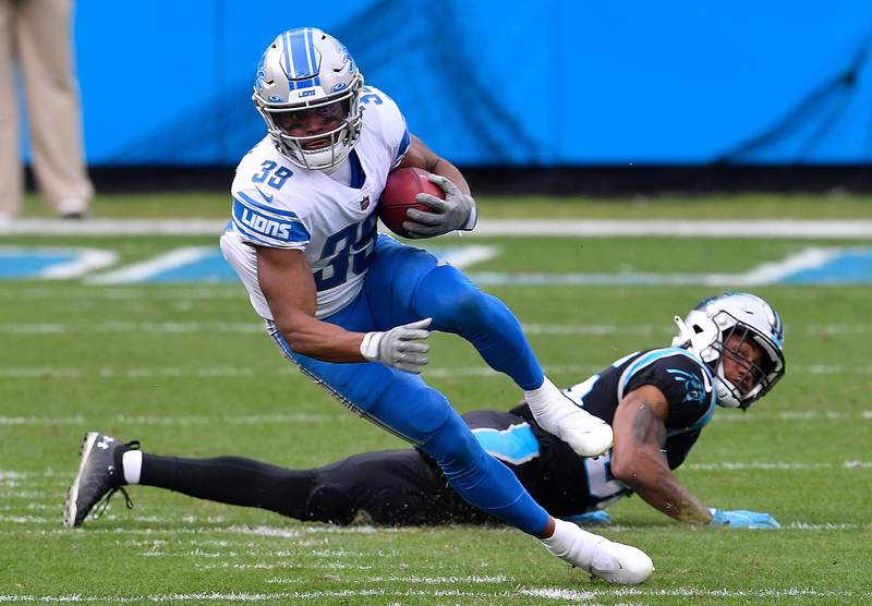 Jamal Agnew #39 of the Detroit Lions attempts to break a tackle by Trenton Cannon #36 of the Carolina Panthers during the first half at Bank of America Stadium on November 22, 2020 in Charlotte, North Carolina. (Photo by Grant Halverson/Getty Images)
