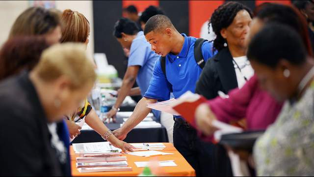 Job seekers check out opportunities at a job fair on June 12, 2014 in Chicago, Illinois.