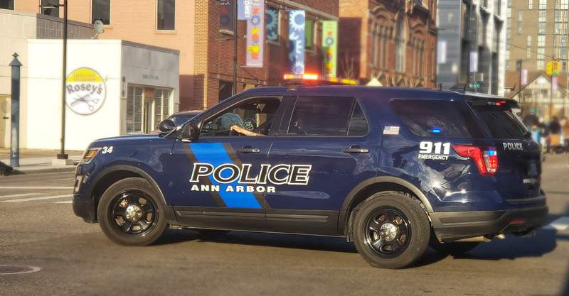 An Ann Arbor Police Department vehicle blocks off part of East Huron Street in downtown Ann Arbor for a march.