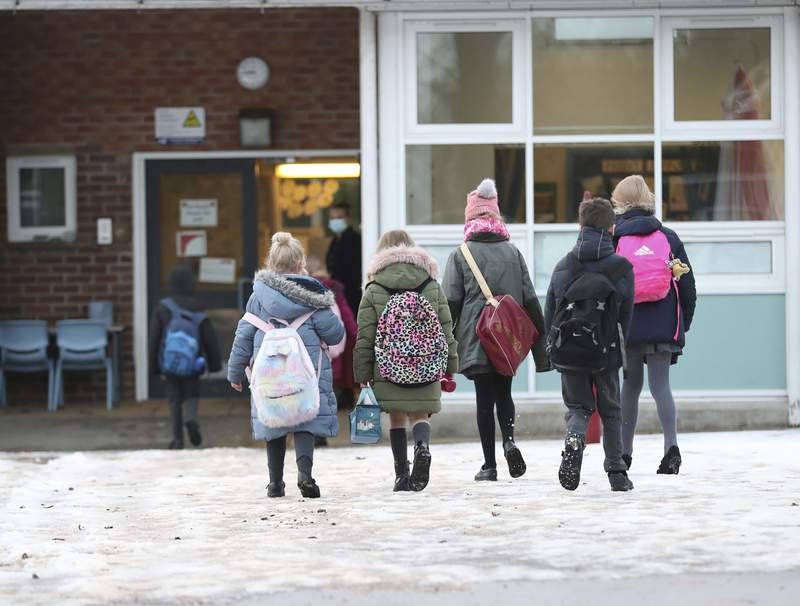 Pupils arrive at Manor Park School and Nursery in Knutsford, England, as schools across England return after the Christmas break, Monday,  Jan. 4, 2021. Britain's Prime Minister Boris Johnson on Sunday insisted he has no doubt that schools are safe and urged parents to send their children back into the classroom Monday in areas of England where schools plan to reopen. (Martin Rickett/PA via AP)