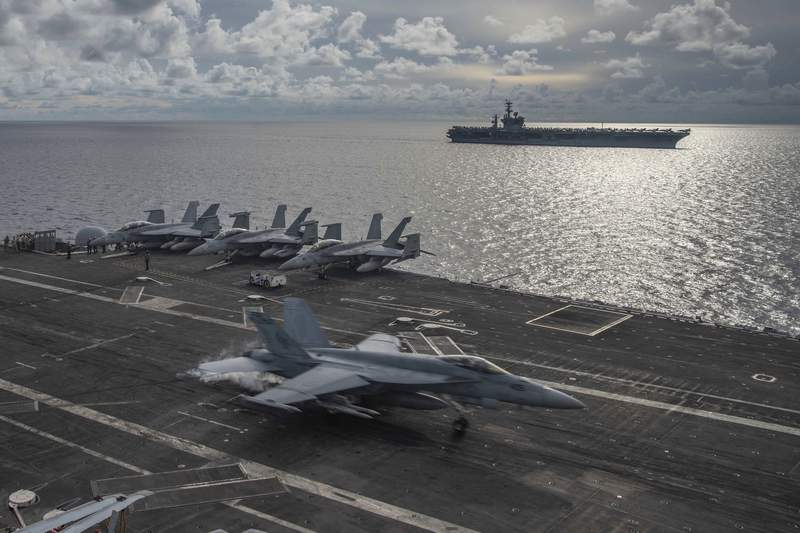 In this photo provided by U.S. Navy, an F/A-18E Super Hornet lands on the flight deck of the USS Ronald Reagan (CVN 76), as USS Nimitz (CVN 68) steams alongside in the South China Sea, Monday, July 6, 2020. Activity by the U.S. Navy in its campaign to challenge Chinas efforts to restrict transit in the South China Sea and in the Taiwan Strait increased sharply over the past two years.  (Mass Communication Specialist 2nd Class Samantha Jetzer/U.S. Navy via AP)