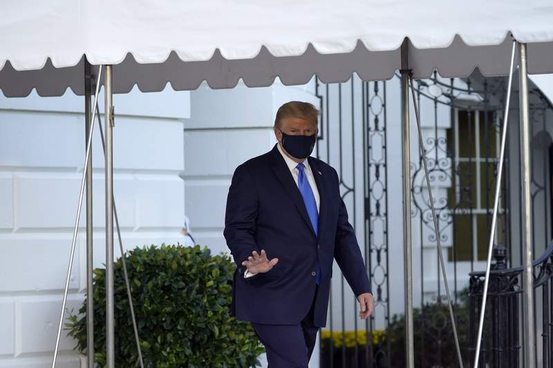 FILE - In this Oct. 2, 2020, file photo President Donald Trump waves to members of the media as he leaves the White House to go to Walter Reed National Military Medical Center after he tested positive for COVID-19 in Washington. Trump told the world that he and first lady Melania Trump had contracted COVID-19 in a tweet at 12:54 a.m. Friday.  (AP Photo/Alex Brandon, File)