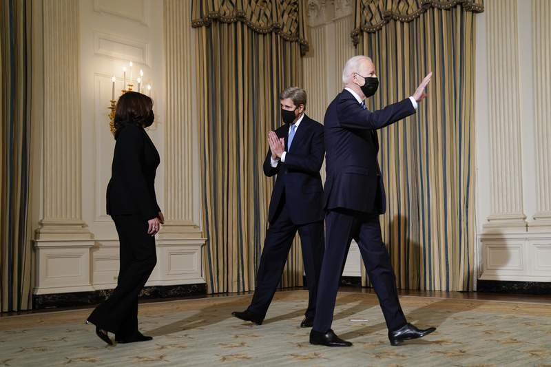 Special Presidential Envoy for Climate John Kerry, center, greets Vice President Kamala Harris as they arrive with President Joe Biden for an event on climate change and green jobs, in the State Dining Room of the White House, Wednesday, Jan. 27, 2021, in Washington. (AP Photo/Evan Vucci)