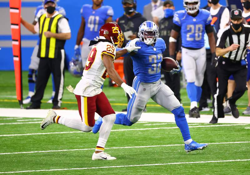 DETROIT, MI - NOVEMBER 15: D'Andre Swift #32 of the Detroit Lions attempts to carry the ball against Kendall Fuller #29 of the Washington Football Team during their game at Ford Field on November 15, 2020 in Detroit, Michigan. (Photo by Rey Del Rio/Getty Images)